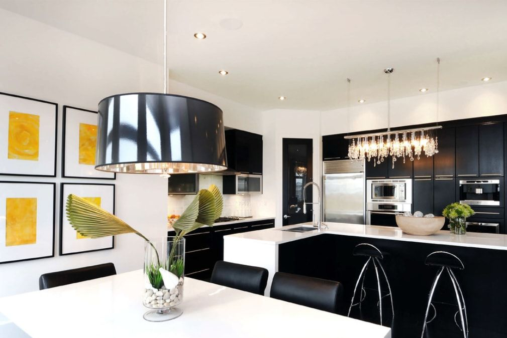 Large kitchen with round chandelier above the dining table and black furniture for contrast