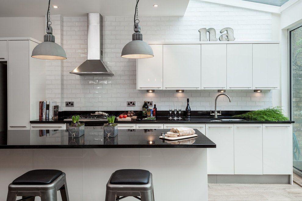 Modern kitchen with underground tile for backsplash and black topped island