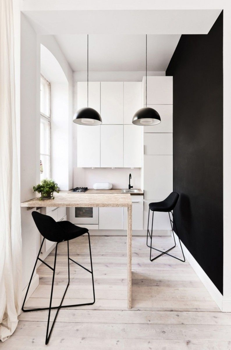 Narrow Scandinavian styled kitchen with black accent wall, lampshades and furniture