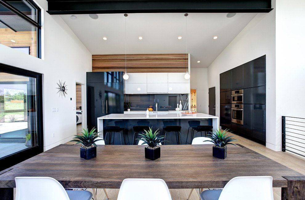 Black and White Interior Combination: Elegant Contrast in Different Rooms. Contemporary kitchen with large wooden table in the dining zone and open layout