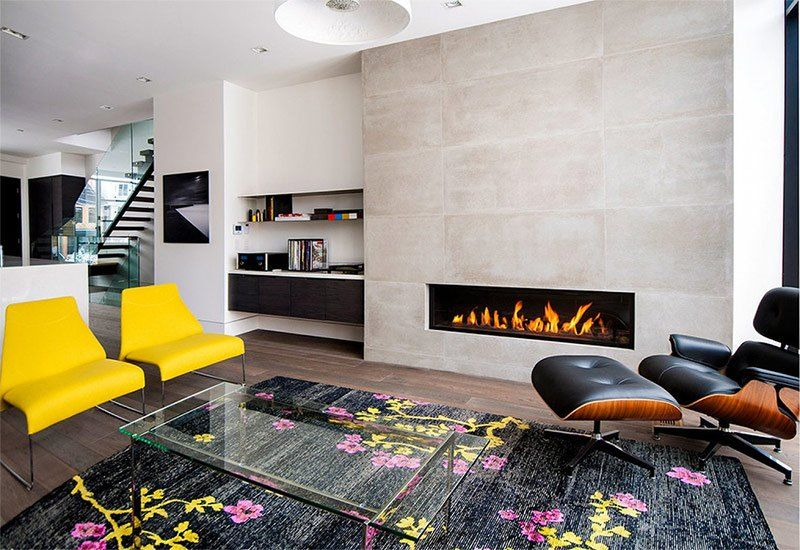 Casual modern design of the living room with different chairs, floral themed rug and the built-in gas fireplace