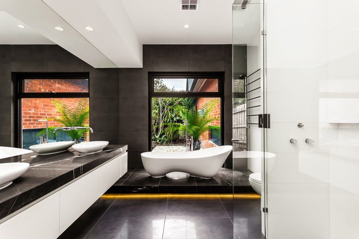 Figured bathtub in the modern bathroom with dark floor and dark accent wall