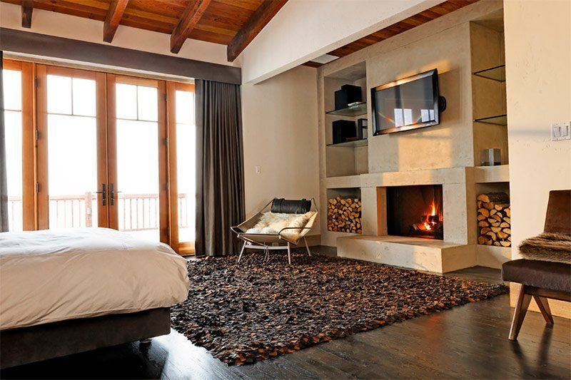 Scandinavian style in large living room with accent wall having firewood racks and the immersed fireplace