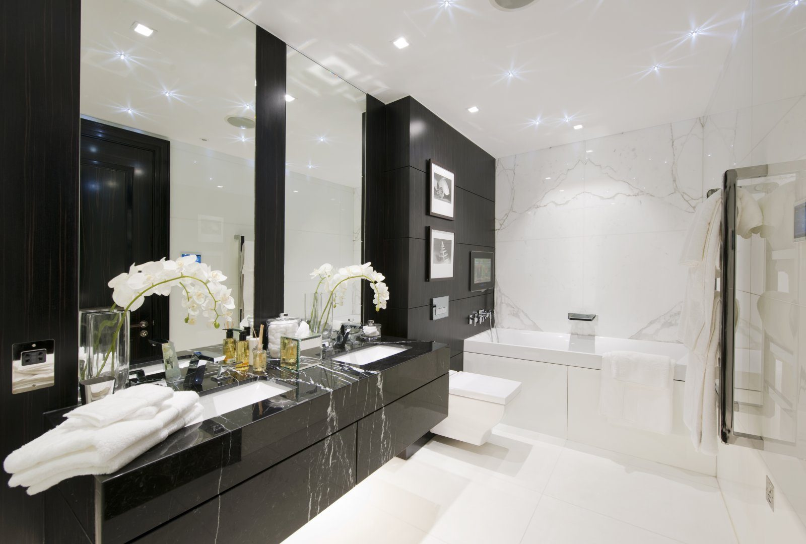 Hypnotic illuminated contrasting large bathroom with dark furniture