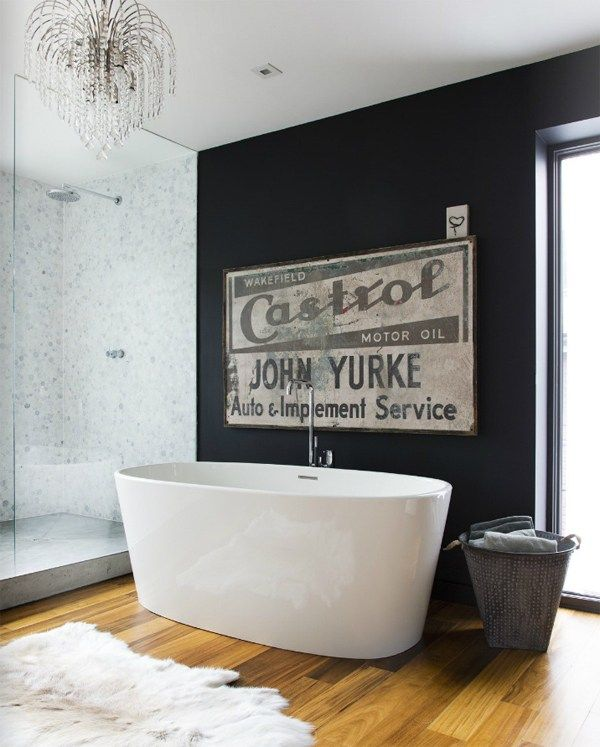 Round stone bathtub at the dark accent wall with large ad board