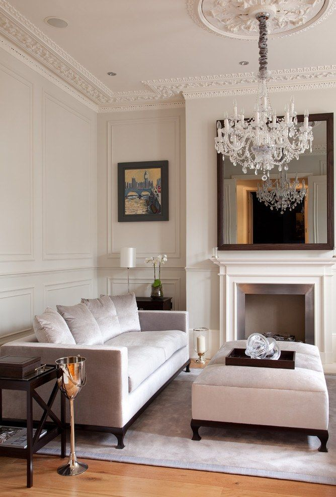 Crystal chandelier, large mirror and other decorative elements in the Classic styled living room with the false fireplace