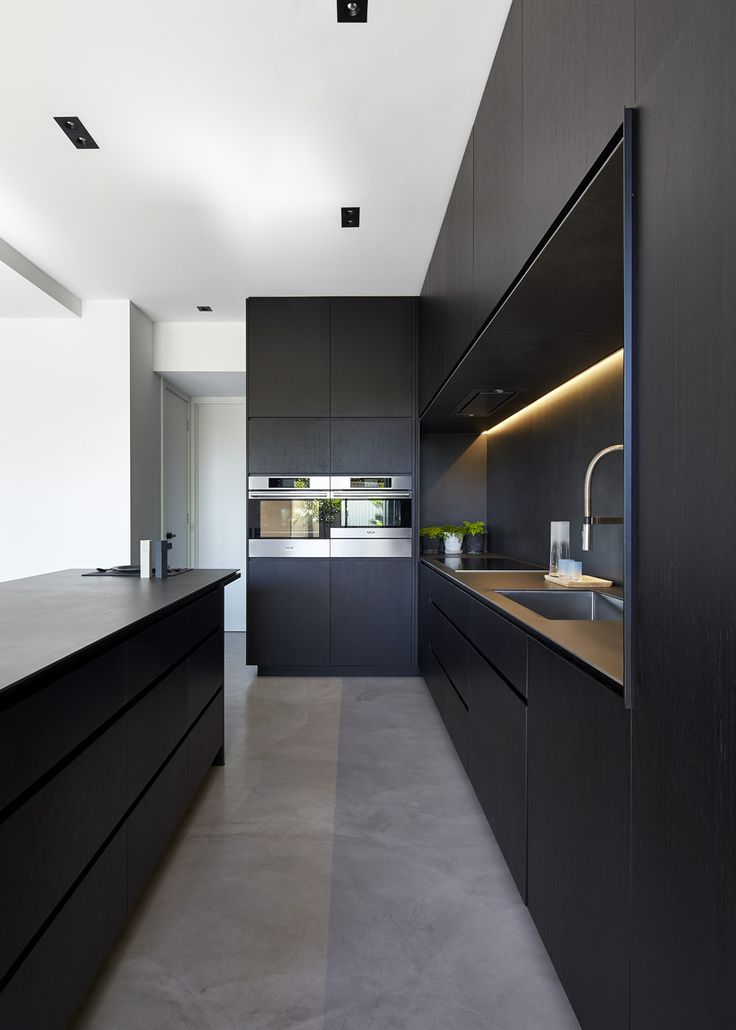 Black kitchen furniture set and island in light decorated modern interior