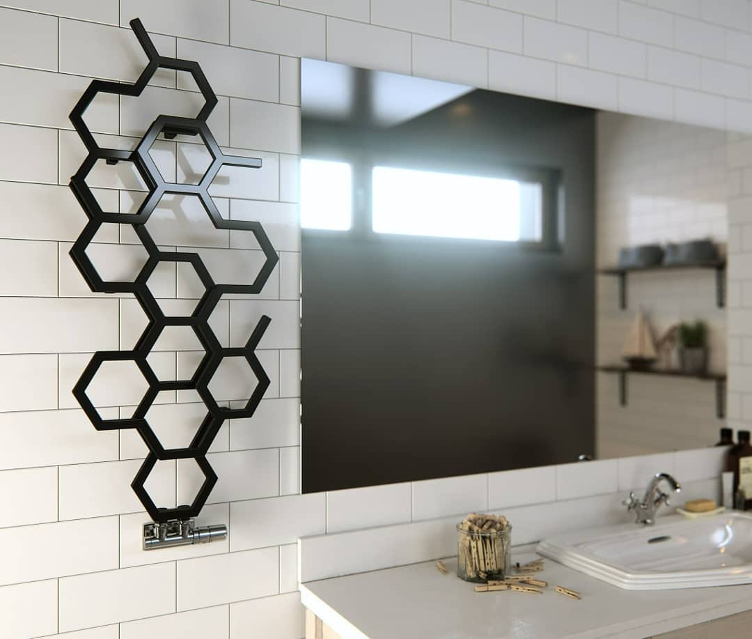 Heated Towel Rail in Bathroom Interior as Practical and Decorative Item. Unusual black honeycomb-looking towel rail for minimalistic bathroom with large mirror