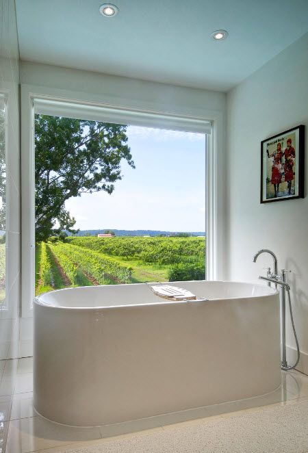 Acrylic Bathtub as the Highlight of Modern Bathroom Interior. Panoramic view of the lawn from the bathroom