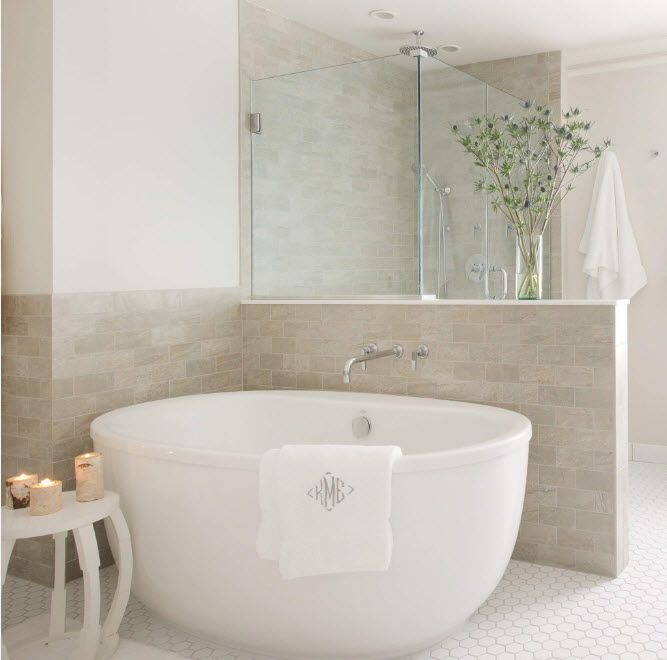 Oval acrylic bathtub in the modern decorated bathroom with marble trimmed low wall zone