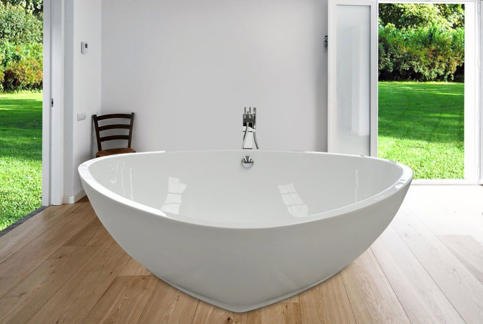 Bathroom with glossy oval shaped bathtub in the laminated floor