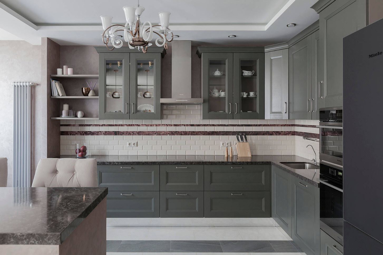 Gray kitchen cabinets with artistically formed facades and vintage chandelier