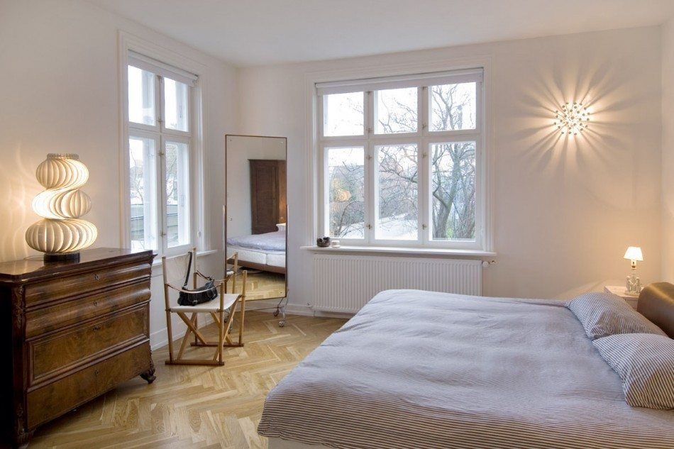 Classical minimalistic bedroom with large mirror and bright lamp