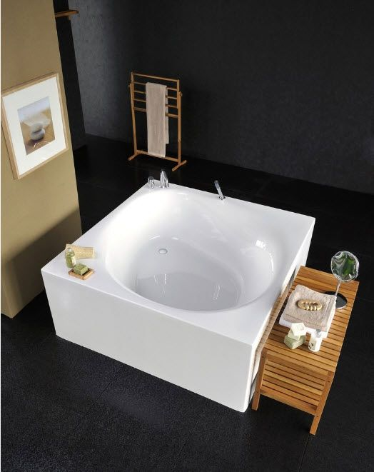 Acrylic Bathtub as the Highlight of Modern Bathroom Interior. Square island of the white bathtub at the dark floor with round form of bath place