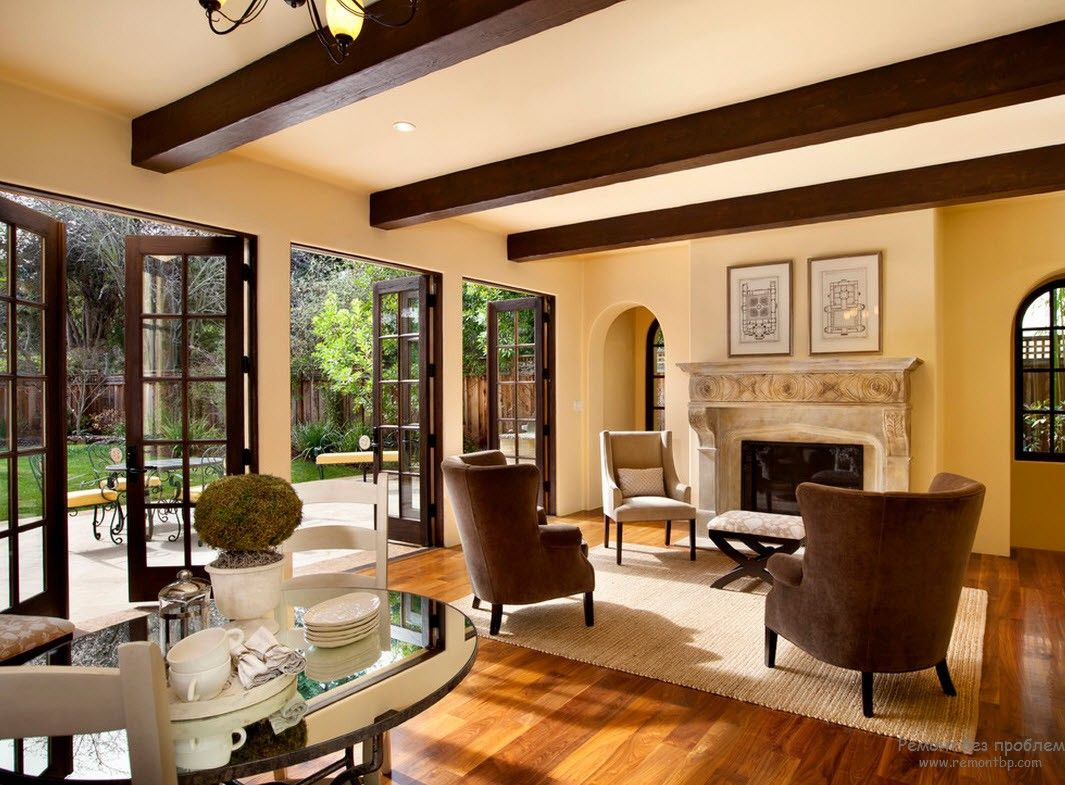 French Interior Design Style Overview. Creamy colored open layout room with chocolate ceiling beams