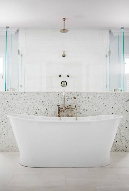 Acrylic Bathtub as the Highlight of Modern Bathroom Interior. Low tier in mosaic and glass screens behind the oval bathtub