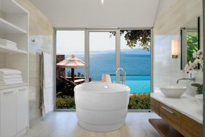 Acrylic Bathtub as the Highlight of Modern Bathroom Interior. Round shaped font at the seashore private house