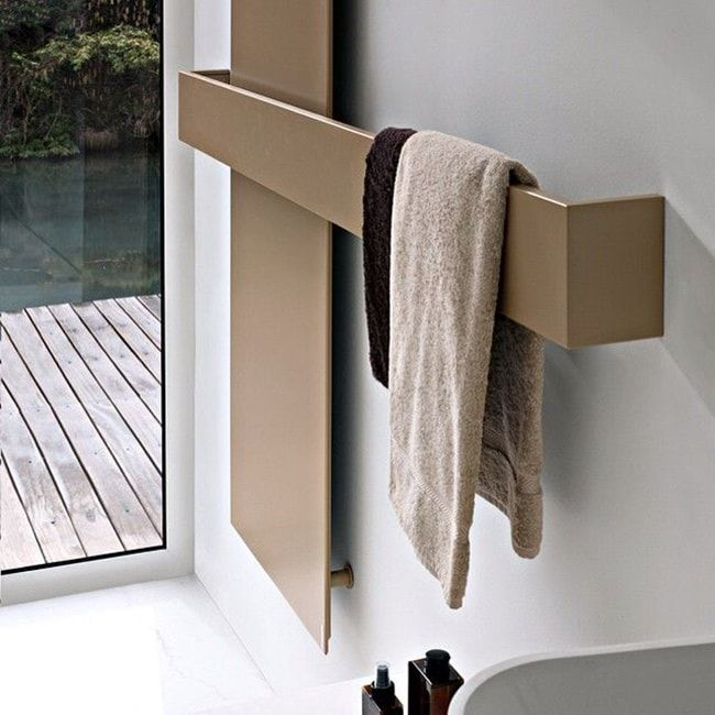 Heated Towel Rail in Bathroom Interior as Practical and Decorative Item. Gilded heated rail for the cottage bathroom interior with palette deck outside