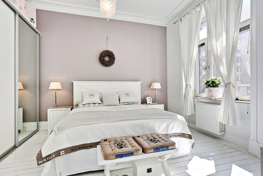 Ottoman at the legboard of the casual styled bedroom in neat pastel colors