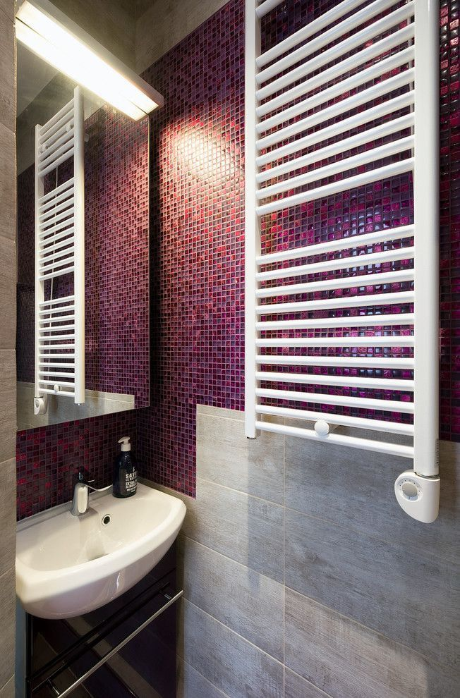 White grid of the heated towel rail in the bathroom with crimson mosaic