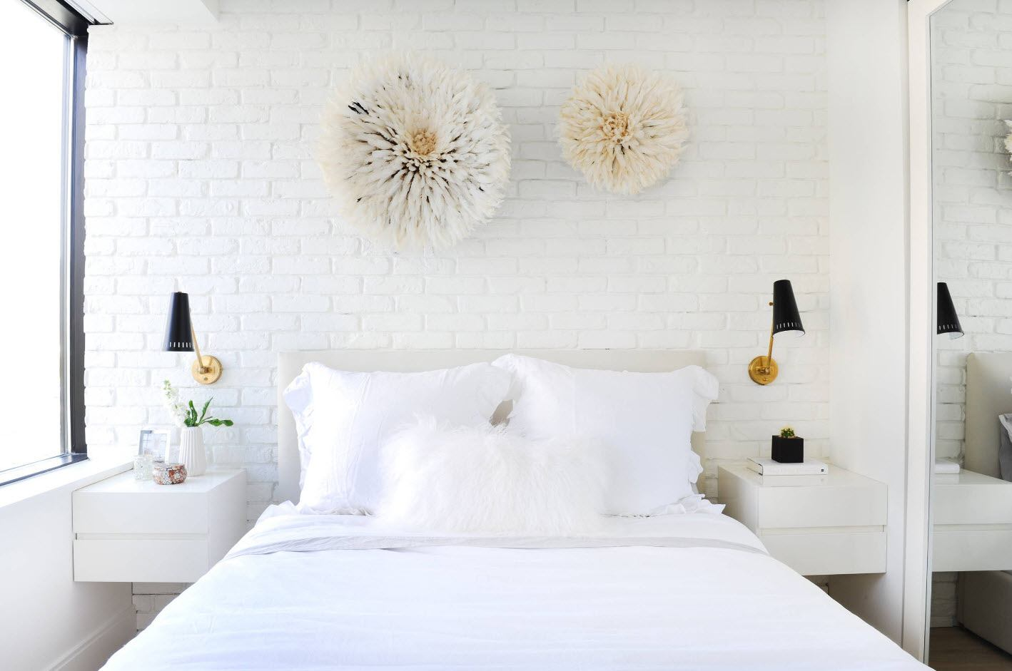 Totally white interior of the bedroom with plates decorating the headboard