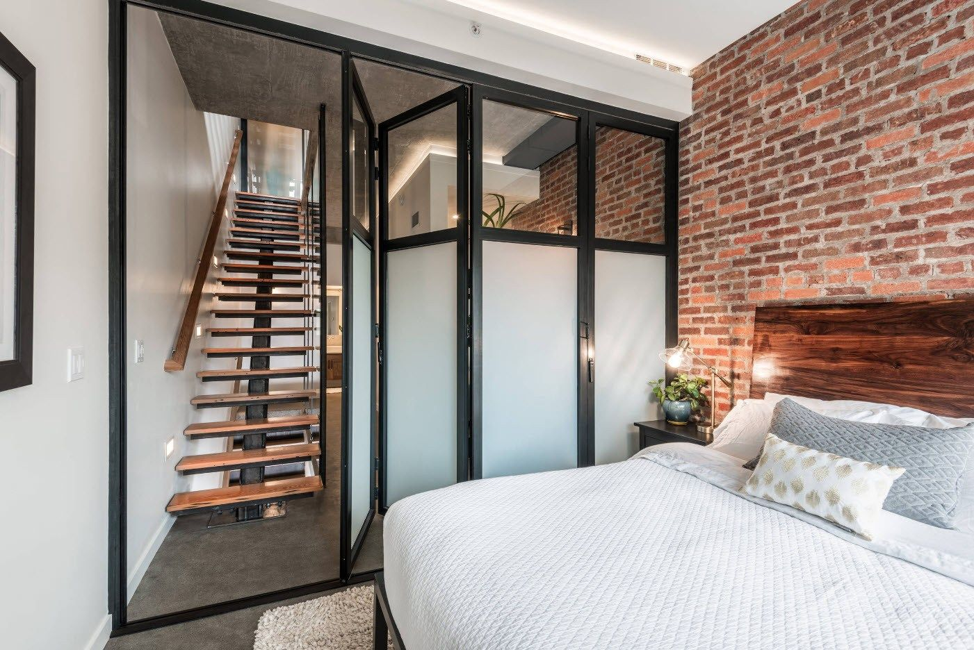 Industrial touc of the modern apartment with brickwork in the bedroom zone