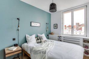 Aquamarine colored accent wall in the modern Scandi styled bedroom interior