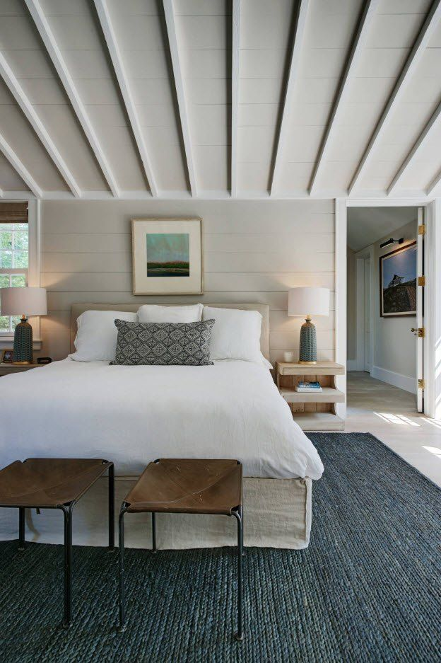 Open ceiling beams and open doors to other rooms in gray designed bedroom