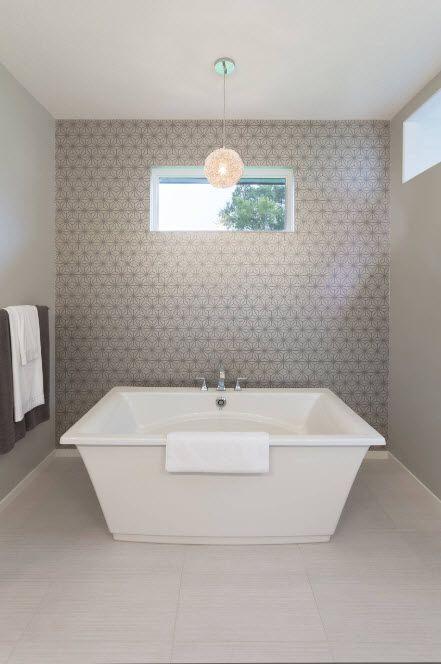 Acrylic Bathtub as the Highlight of Modern Bathroom Interior. Gray tiled bathroom with snow-white bathtub