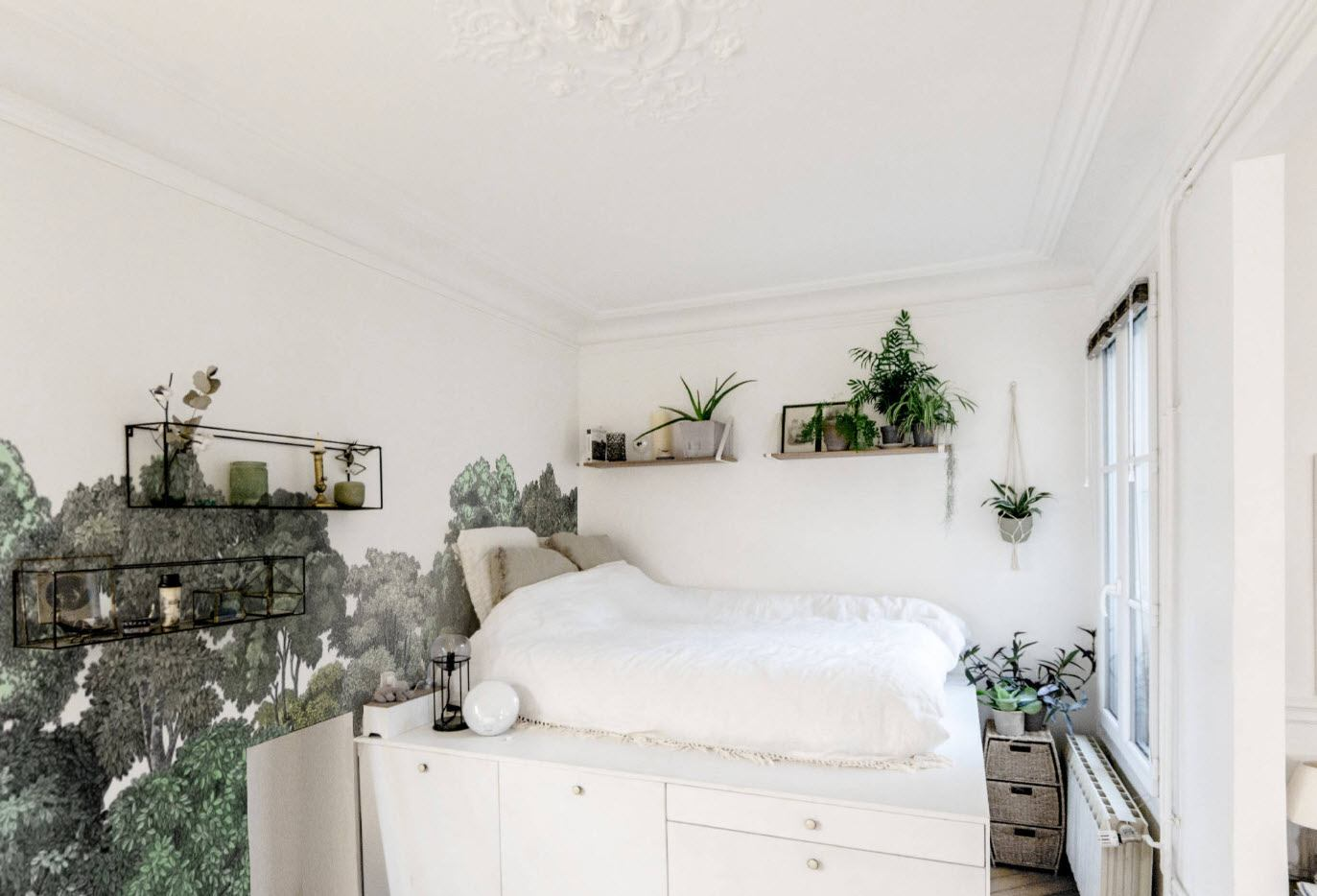 White Scandi bedroom with the bed on storage pedestal