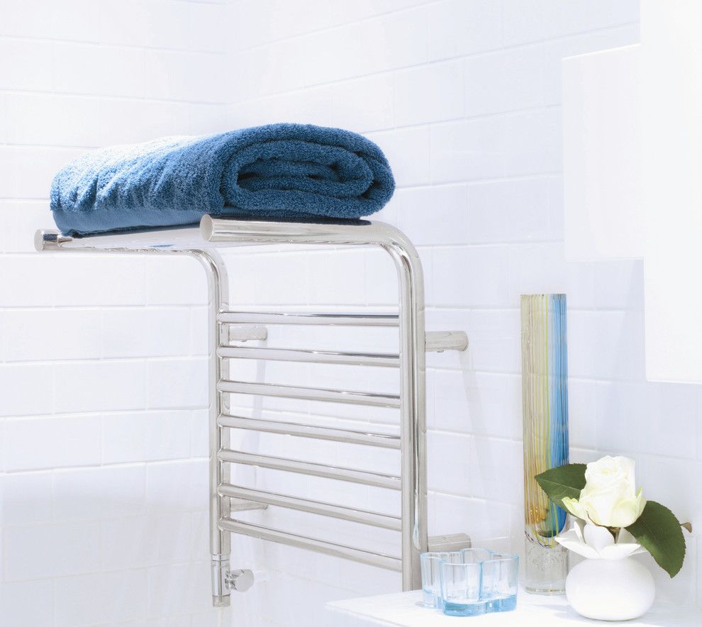 Heated Towel Rail in Bathroom Interior as Practical and Decorative Item. Neat decoration of the bathroom in white with steel glossy towel heater