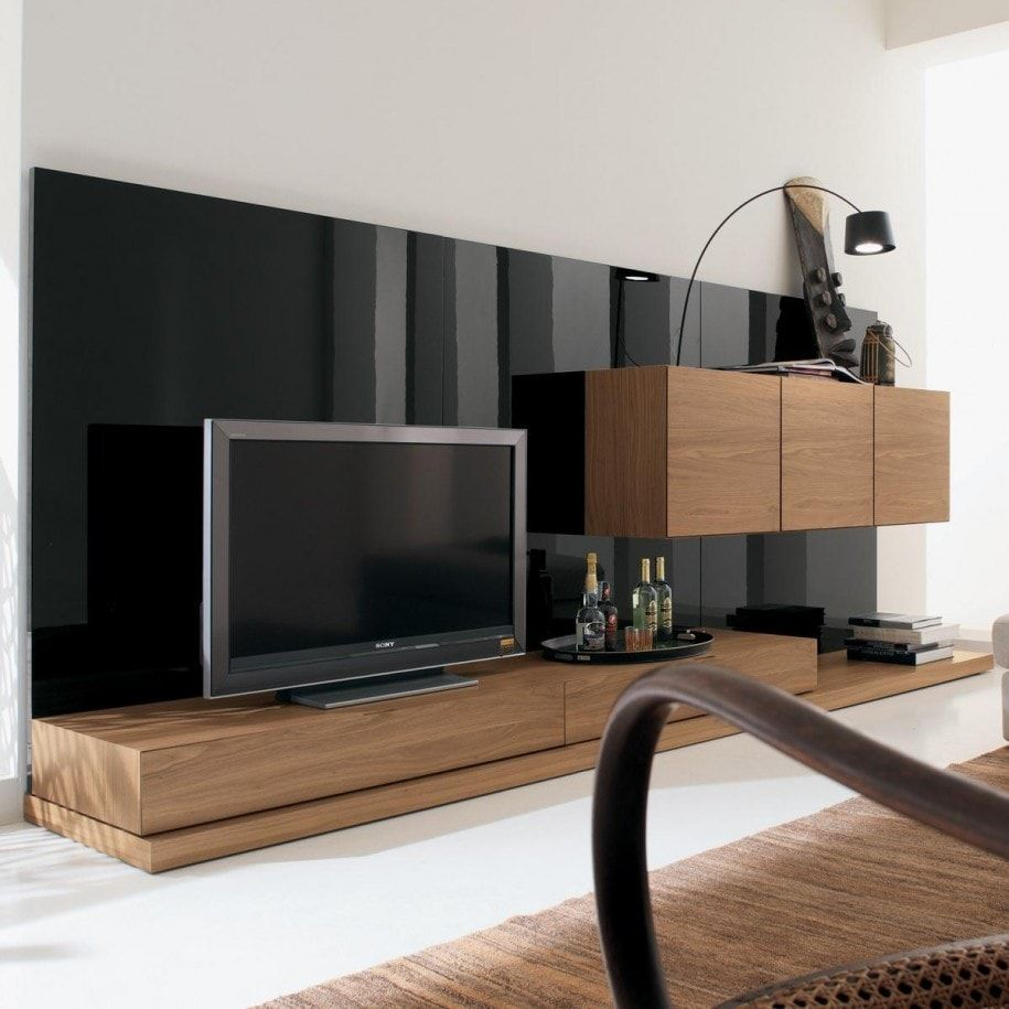 BLack mirroring accent wall of plastic in the living room with brown wooden furniture