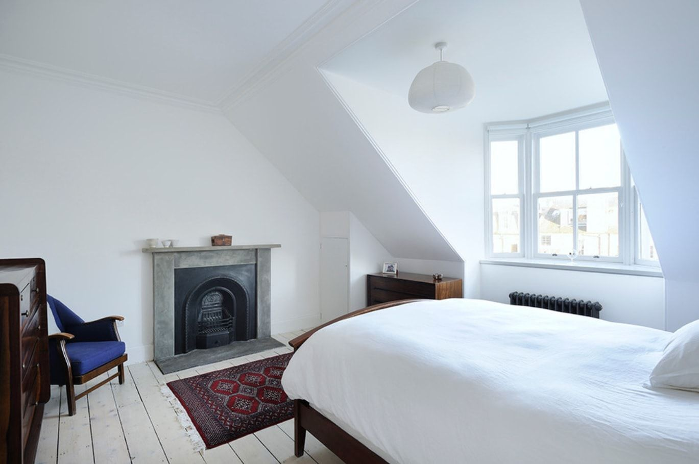 Bedroom at the attic with decorative fireplace