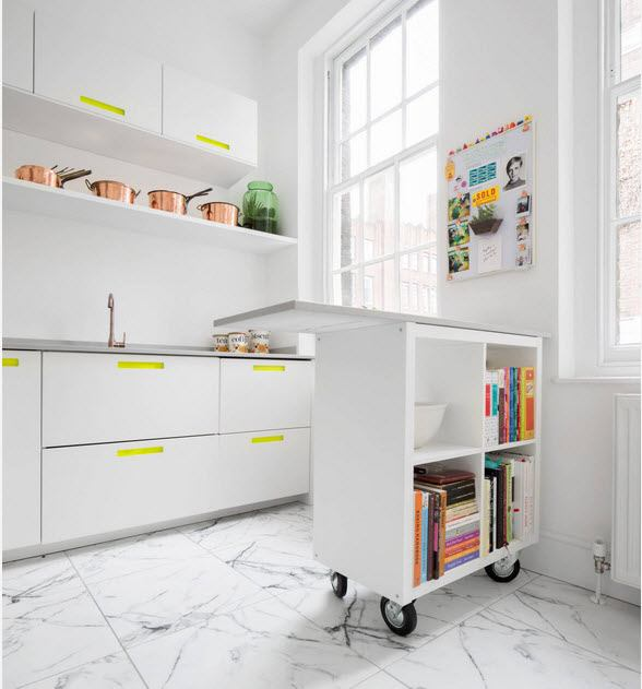 Snow white kitchen with colorful interior elements and mobile table on castors
