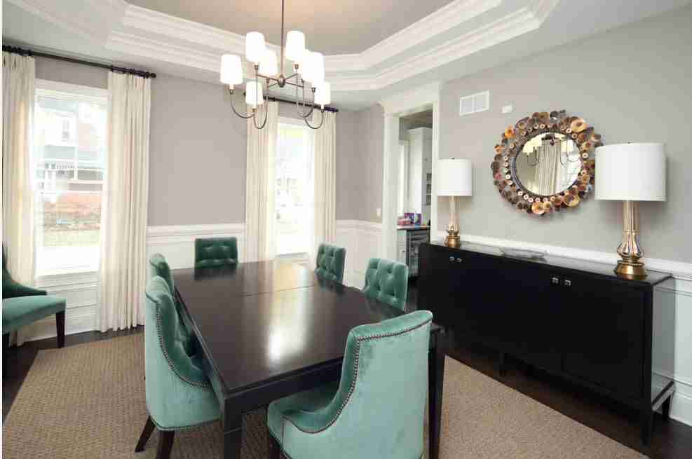Black colored chest of drawers in the dining room with turquoise set of chairs