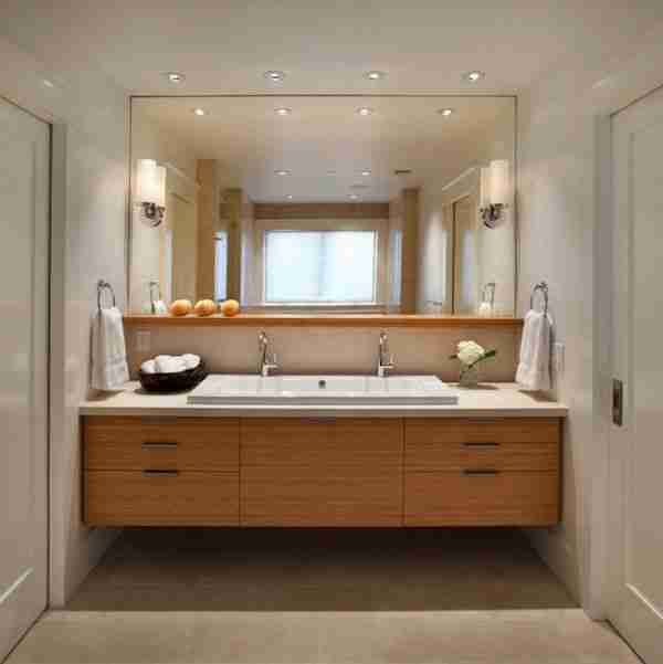 Minimalistic eco style for the light tiled bathroom with light wooden vanity and large mirror