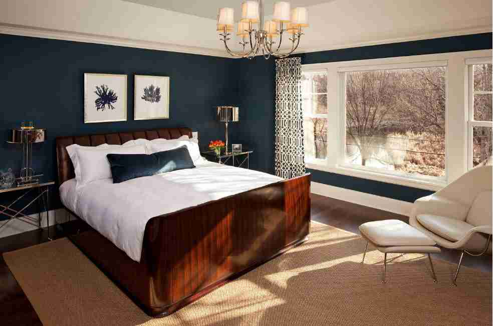 Dark blue wall decoration in the classic bedroom with dark wooden bed