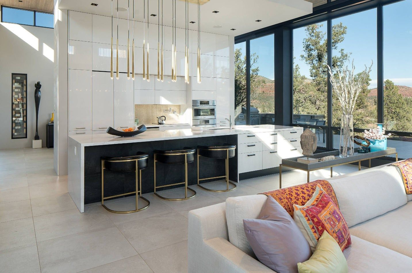 The row of pendant lamps over the cooking top of modern light kitchen