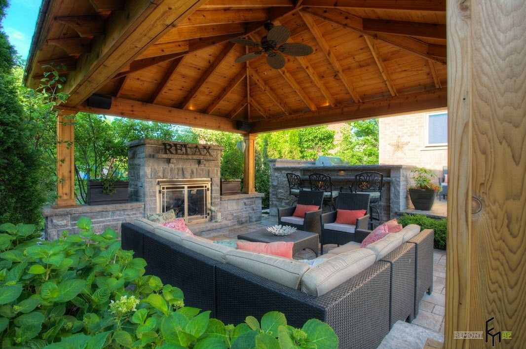 Backyard and Garden Gazebo: Design, Form, Use and Practical Advice. Leather upholstered outdoor furniture and the large canopy with straw roof