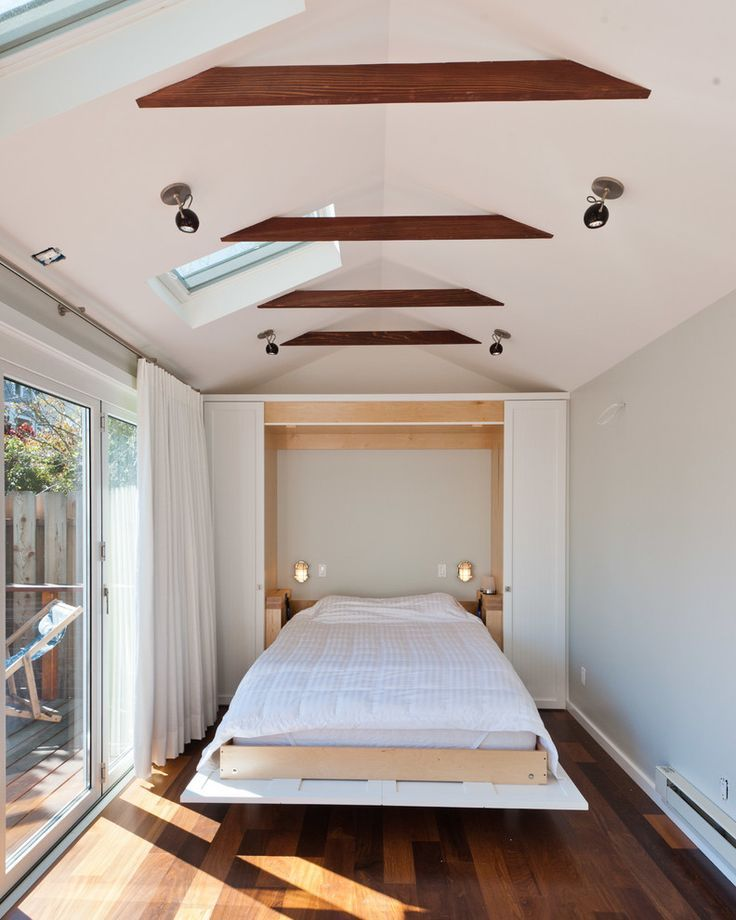 Dark open ceiling beams and totally white interior decoration and bed in the wall recess