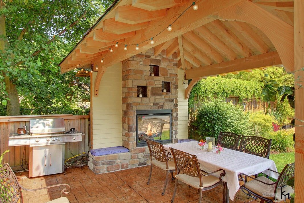 Backyard and Garden Gazebo: Design, Form, Use and Practical Advice. Light wooden gazebo with the stone oven
