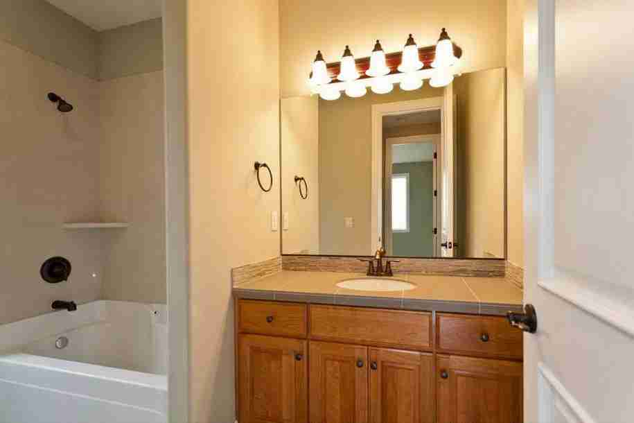 Exposed lamps to light the mirror in classic bathroom