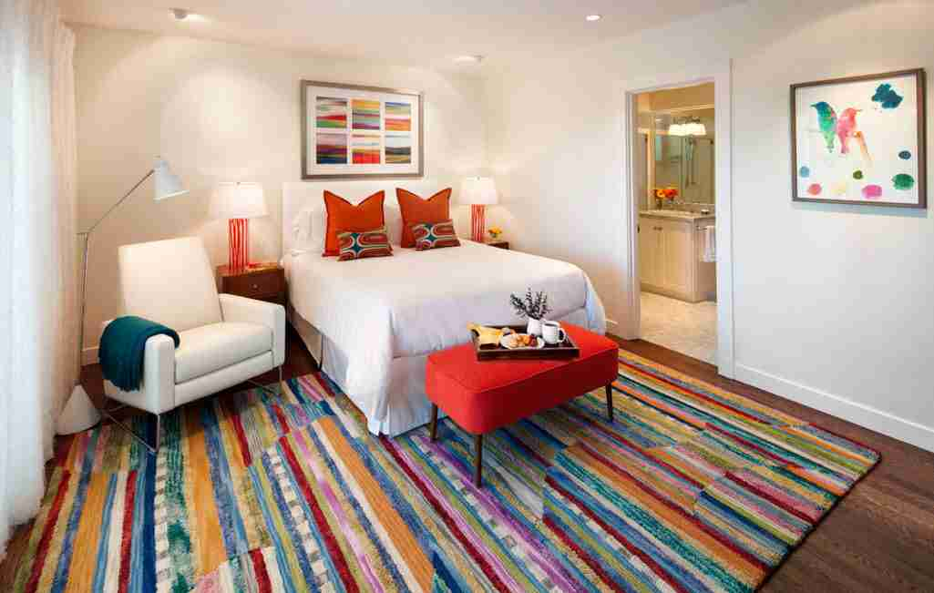 Small bedroom with colorful carpeting