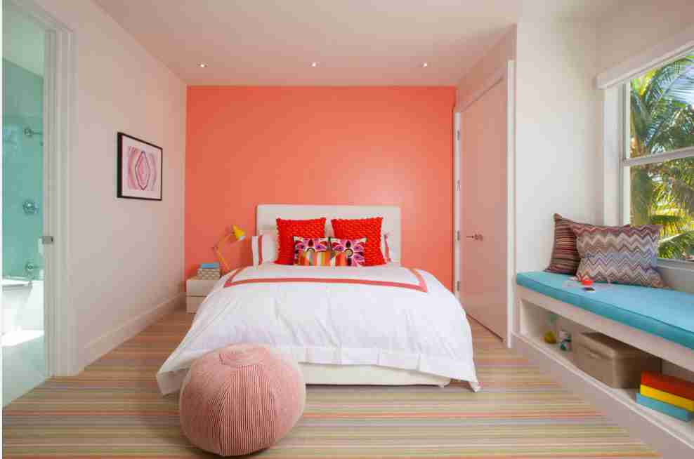 Orange finished wall in the bedroom with low bed and fluffy soft ottoman