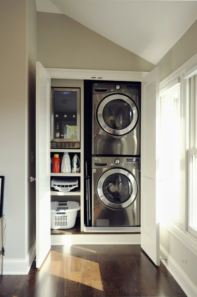 Washing and drying machines in the recess of walls of the gray designed room