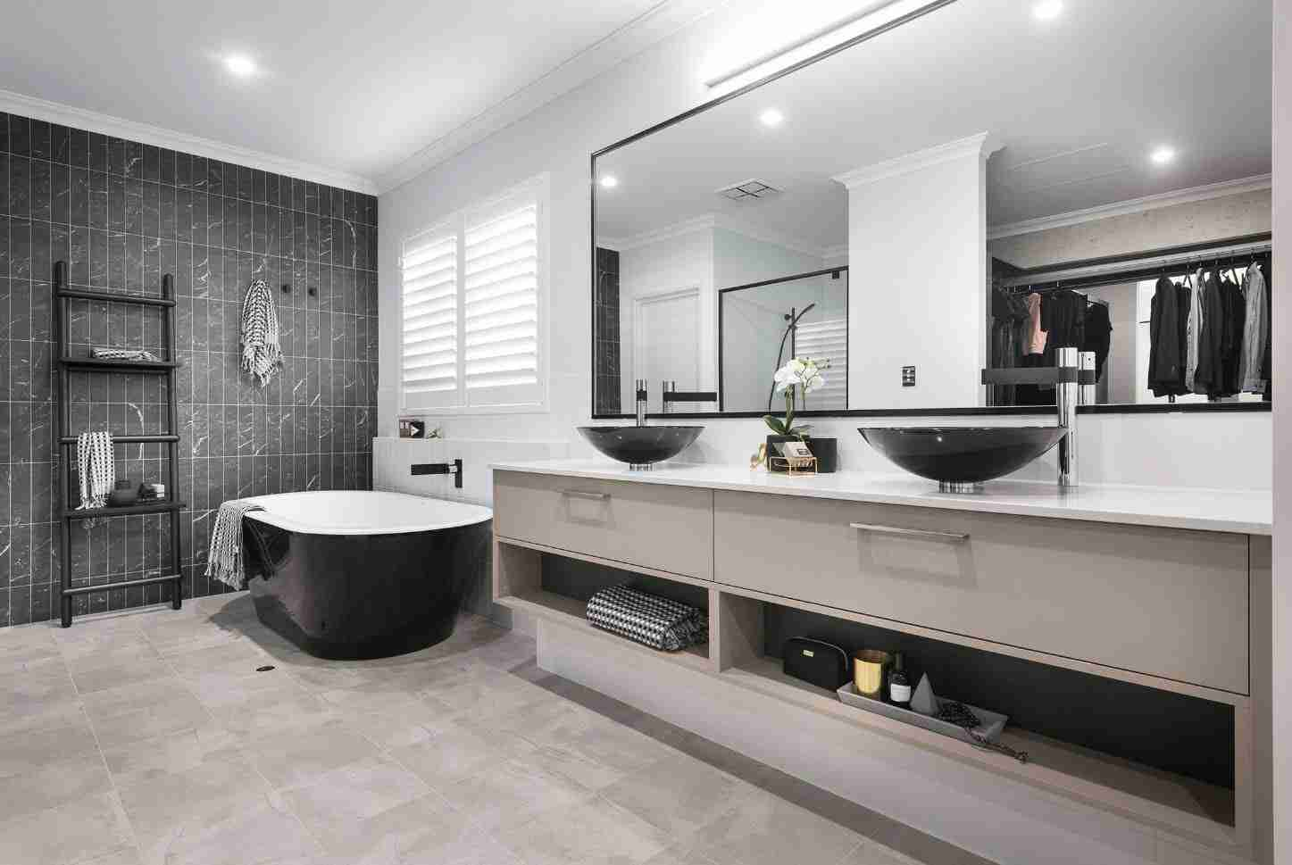 Large mirror in the Scandinavian styled bathroom interior with black bathtub and vanity for two people