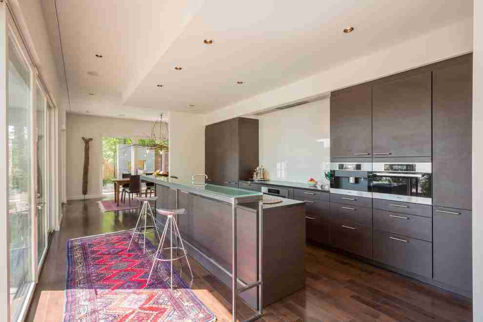 Solid Wood Kitchen Stylish Ideas for Modern Interiors. Gray kitchen cabinets and island for hi-tech designed kitchen with colorful rug
