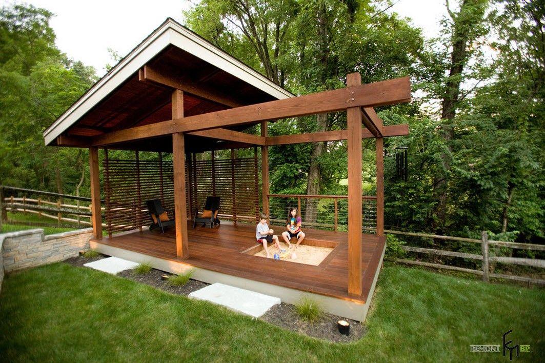 Open wooden framed gazebo with the sandbox for children