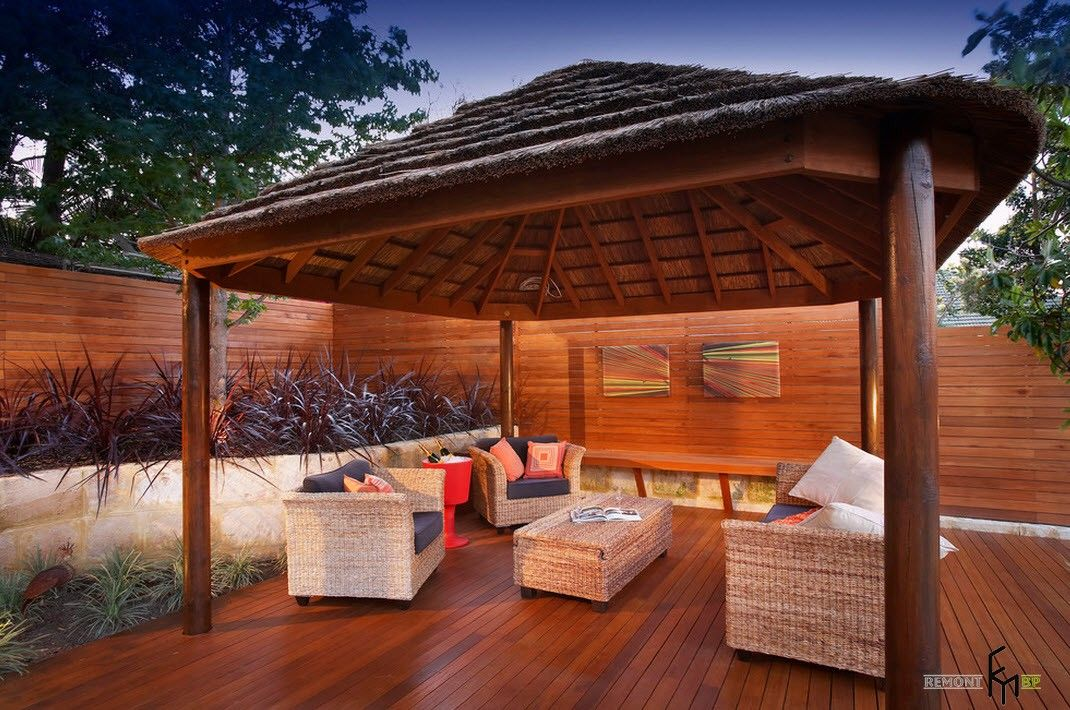 Straw roof for the modern designed gazebo on the walnut platform and with white soft furniture