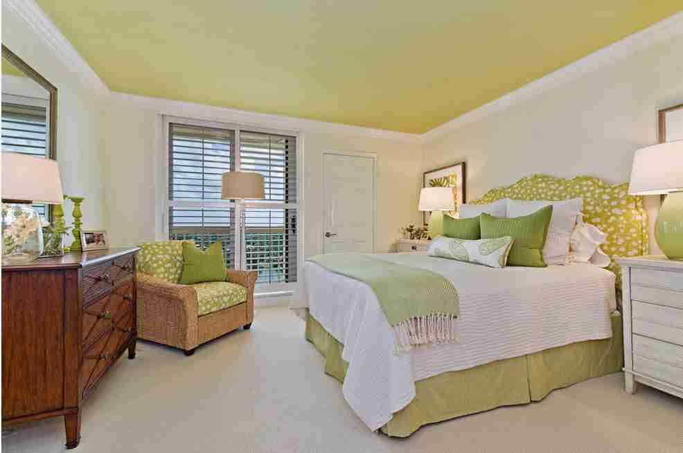 Unexpectedly lime colored ceiling in white bedroom